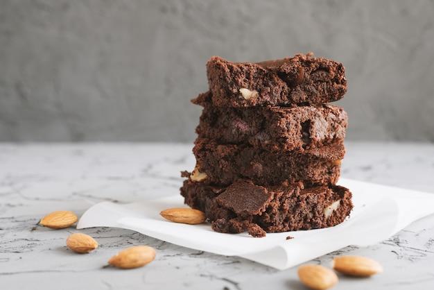 콘크리트 테이블에 있는 종이에 아몬드를 넣은 초콜릿 브라우니 케이크