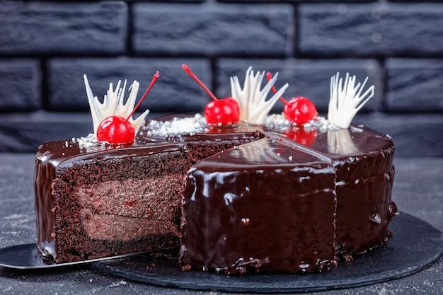 チェリーパイのチョコレートブラウニーケーキの上にダークチョコレートの釉薬を詰め、缶詰のチェリーで飾ったi