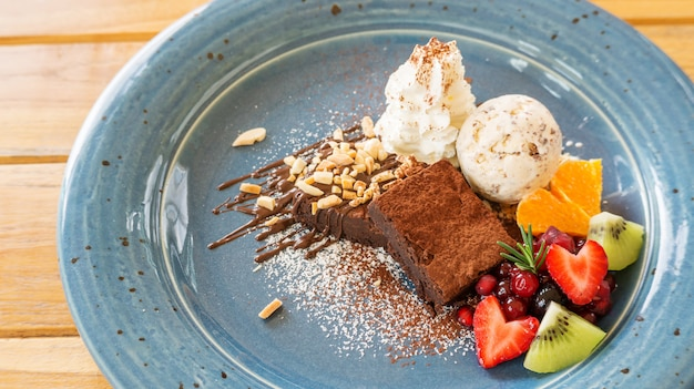 Chocolate brownie cake with ice cream and mix fruit on a blue plate.