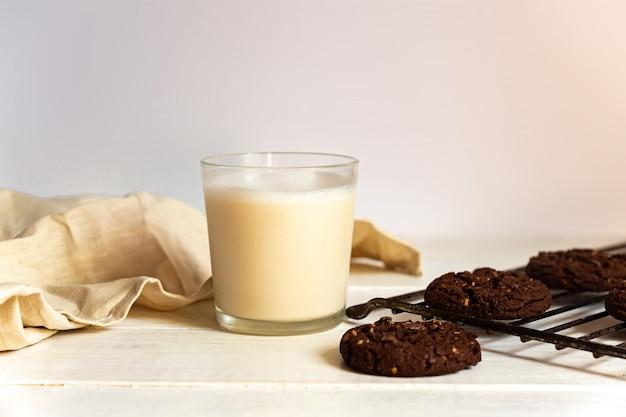 チョコレートブラウニークッキーと木製の背景にココナッツミルクのガラス。自家製ペストリー。