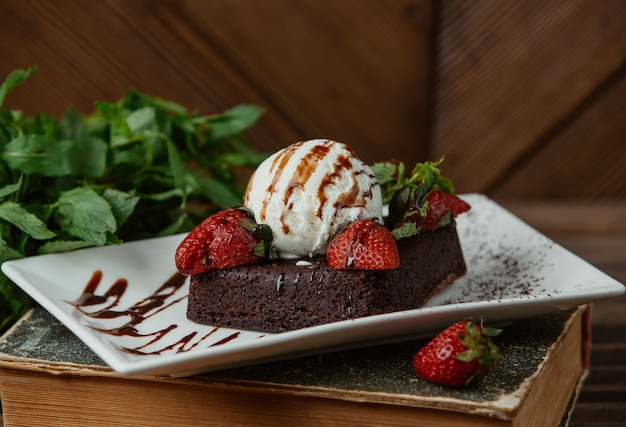 Chocolate brownie served with vanilla icecream ball and strawberries