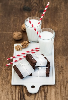 Chocolate brownie slices wrapped in paper and tired with rope, glasses of milk, stripe straws, walnuts on white ceramic board over rustic wooden