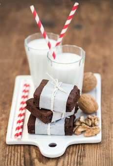 Chocolate brownie slices wrapped in paper and tired with rope, glasses of milk, stripe straws, walnuts on white ceramic board