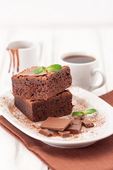 Chocolate brownie square pieces in stack on white plate decorated with mint leaves and cocoa powder