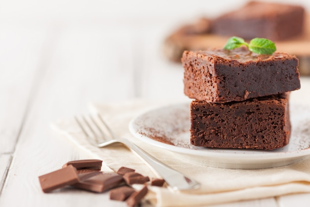 Chocolate brownie square pieces in stack on white plate decorated with mint leaves