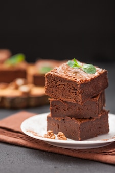 Chocolate brownie square pieces in stack on white plate with walnuts, decorated with mint leaves