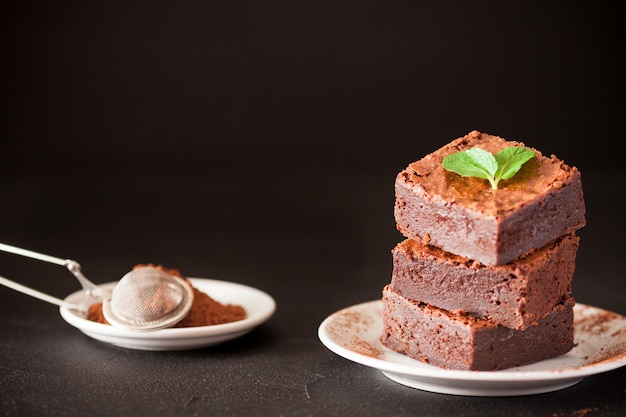 Chocolate brownie square pieces in stack on white plate with walnuts