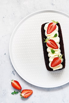 Chocolate brownie with airy vanilla cream and fresh strawberries. chocolate cake with cream and fresh berries.