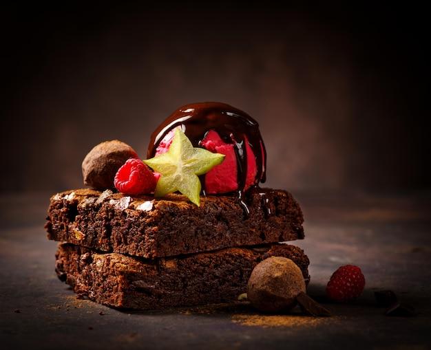 Chocolate brownie with chocolate ice cream and fruit.