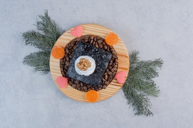Шоколадное пирожное с кофейными зернами на деревянной тарелке.
