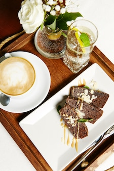 Chocolate brownie with cream, a cup of cappuccino, a glass of water with lemon on a tray. healthy breakfast