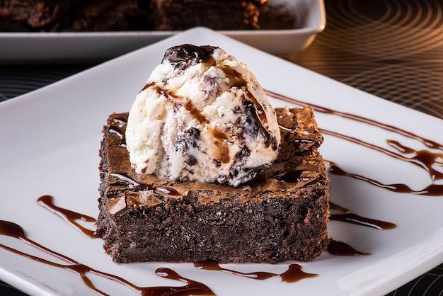 Шоколадный брауни с мороженым на тарелке