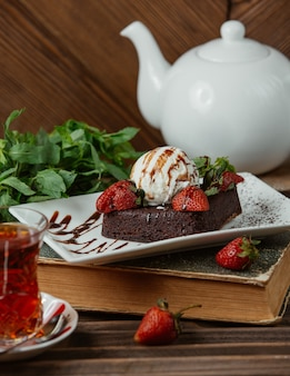 Chocolate brownie with icecream ball and strawberries , and a glass of tea