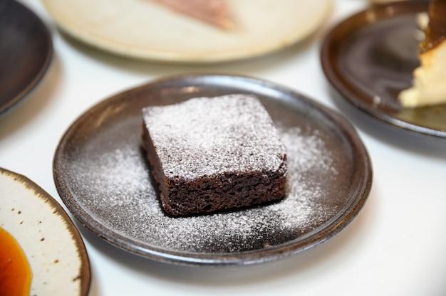 Chocolate brownie with icing powder on dish