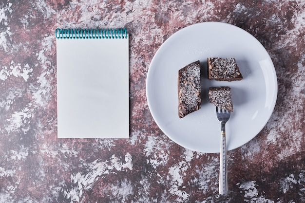 Chocolate brownie with a recipe book aside.