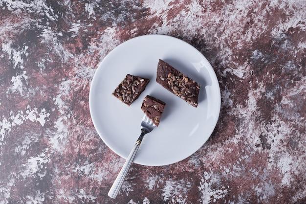 Шоколадные пирожные в белой тарелке, вид сверху.