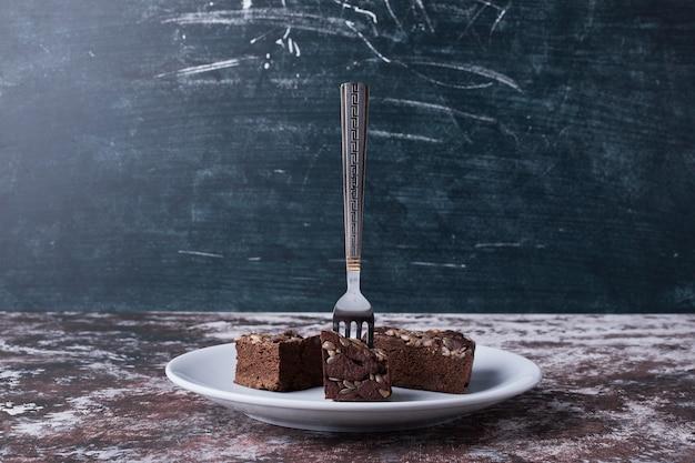 それのフォークで白い皿にチョコレートのブラウニー。