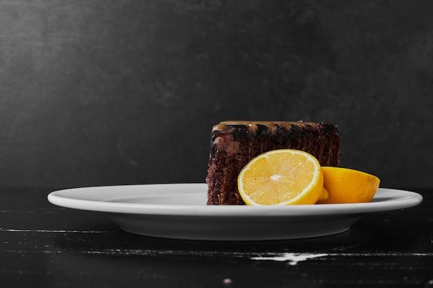 レモンと白いプレートのチョコレートブラウニー。