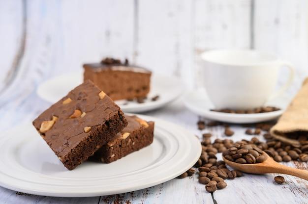 Пирожные шоколада на белой плите и кофейные зерна на деревянной ложке.