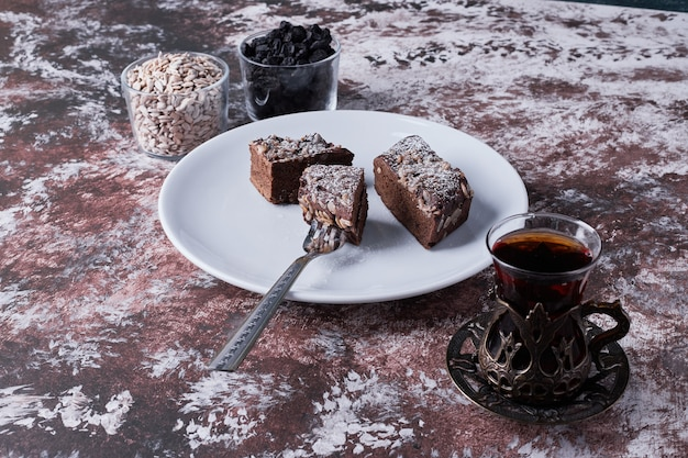 Chocolate brownies served with a glass of tea.