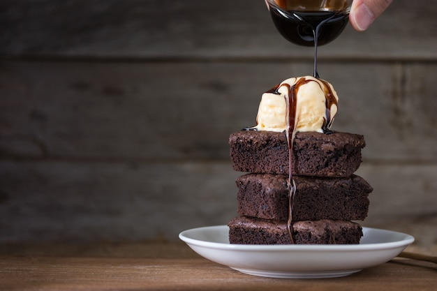 Chocolate brownies stacks and vanila ice cream on top, wooden