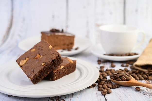 Chocolate brownies on a white plate and coffee beans on a wooden spoon.