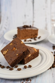 Chocolate brownies on a white plate and coffee beans.