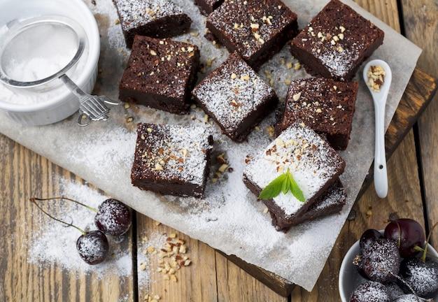 Шоколадные пирожные с сахарной пудрой и вишней на темном деревянном фоне. выборочный фокус.