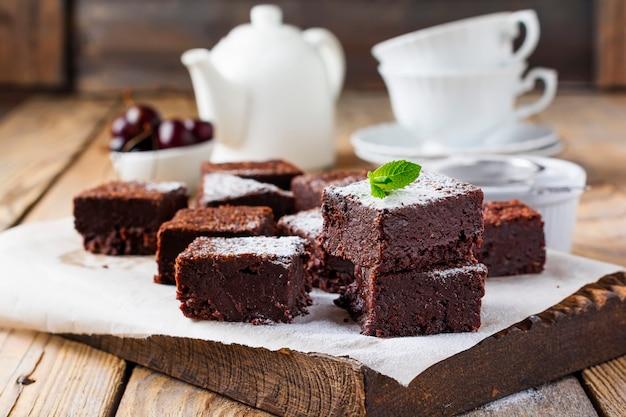 Шоколадные пирожные с сахарной пудрой и вишней на темной деревянной поверхности. выборочный фокус.