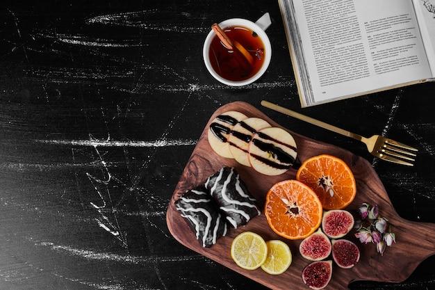 제철 과일과 차 한 잔을 곁들인 초콜릿 브라우니.