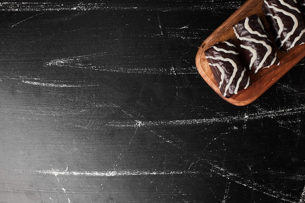 Chocolate brownies on a wooden platter .