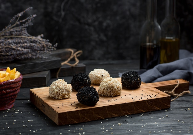 Chocolate buns covered with truffles on a wooden board