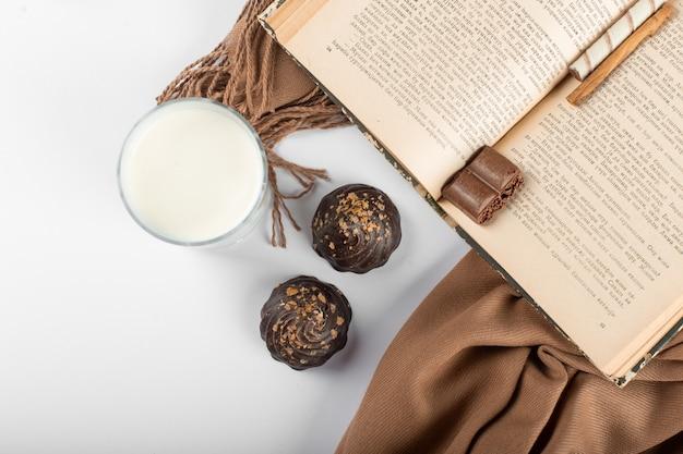 ミルクのガラスと本を脇に置いたチョコレートパン。上面図
