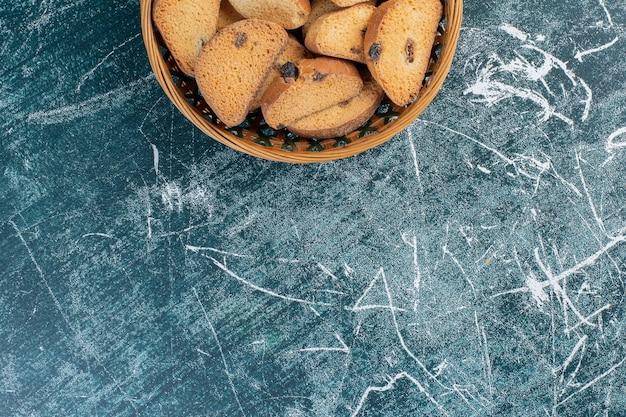 Biscotti al burro al cioccolato sulla superficie blu.
