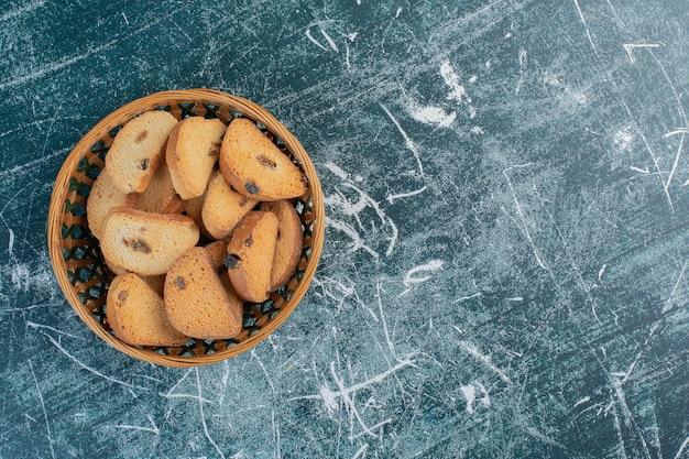 Cracker di burro al cioccolato su superficie blu.