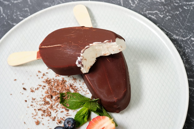 Chocolate butter ice cream popsicles on the white plate with fresh summer berries, strawberries, blueberries
