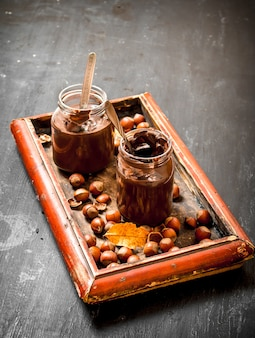 Chocolate butter with hazelnuts on a black chalkboard