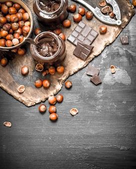 黒い黒板にヘーゼルナッツとチョコレートバター