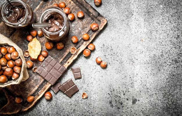 素朴な背景にヘーゼルナッツとチョコレートバター