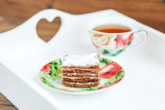 チョコレートケーキと白いお皿の上の熱いお茶のカップ。