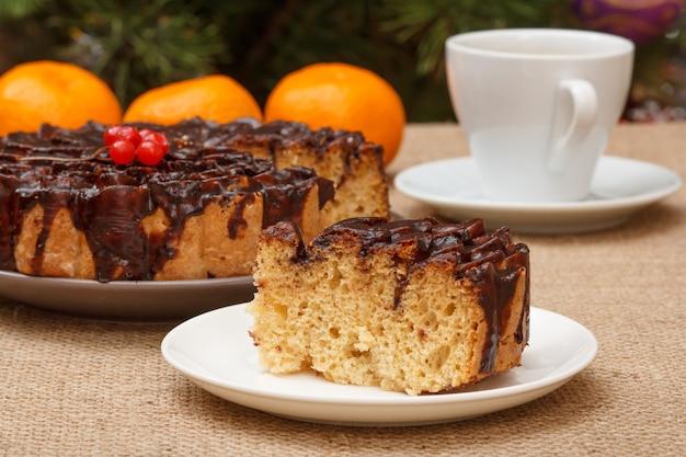 Шоколадный торт и его кусок на тарелке с чашкой кофе и апельсинами на заднем плане.