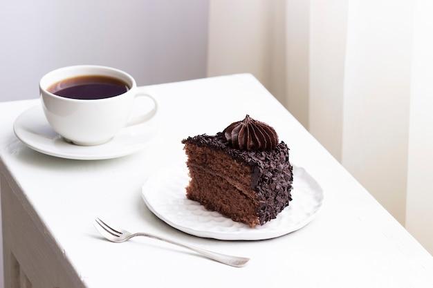 チョコレートケーキとコーヒー、明るいインテリアの静物。セレクティブフォーカス。