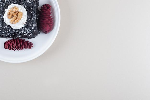 大理石の背景の大皿にチョコレートケーキと赤い松ぼっくり。