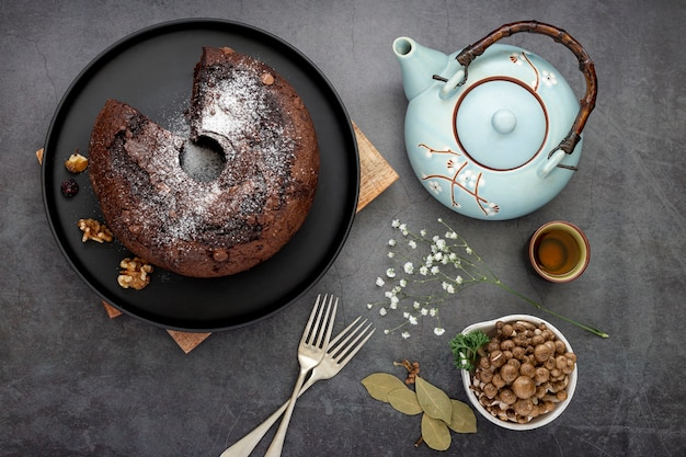 Chocolate cake on a black plate with a tea kettle