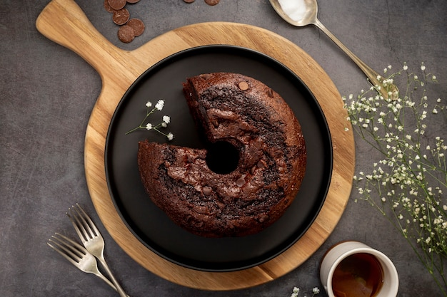 Chocolate cake on a black plate and a wooden support on a grey background