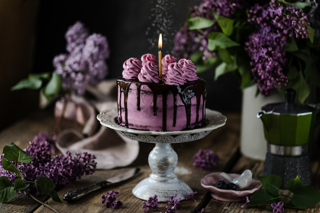 Chocolate cake and a bouquet of lilacs on wooden table
