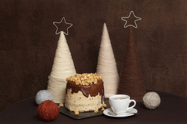 Chocolate cake, caramel and popcorn, cup of tea, decorated table
