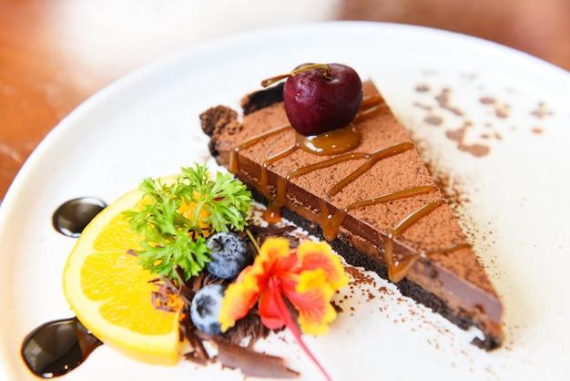 Карамельный шоколадный торт с вишней и фруктами на белой тарелке