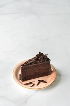 Chocolate cake. chocolate fudge cake on pink plate. cake on white marble background.
