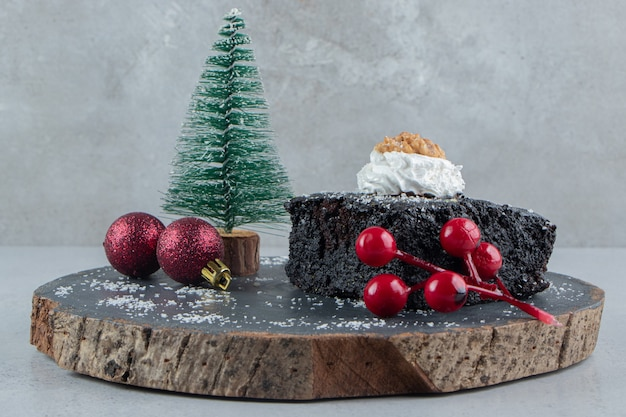 Chocolate cake and christmas decorations on a wooden board on marble background.